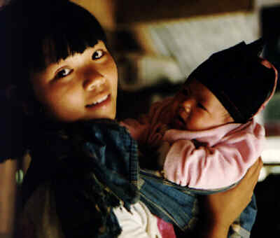 Appa, an Akha girl from Burma, with her baby